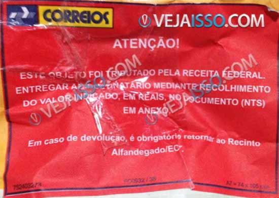 Exemplo de encomenda tributada pela receita federal - Adesivo vermelho é colado que indica que sua encomenda foi taxada imposto de importação alfândega